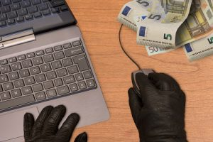 Computer crime metaphor, hand in black gloves with mouse, computer and banknotes.